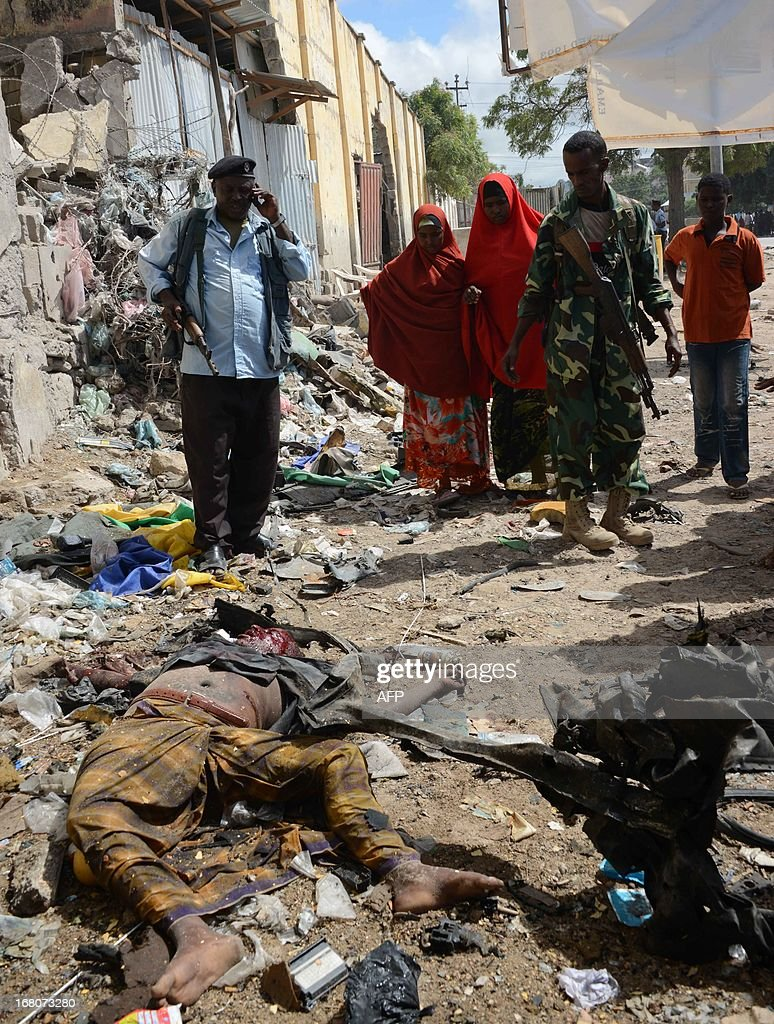 Security surround the area following a suicide attack on a government convoy in Mogadishu on May 5, 2013. Around 11 people were killed today when a suicide attacker rammed a car laden with explosives into a government convoy at a busy junction in the Somali capital, police said. AFP PHOTO/