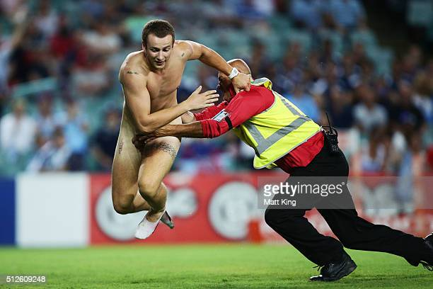 Security tackle a streaker on the playing field during the round one Super Rugby match between the Waratahs and the Reds at Allianz Stadium on...