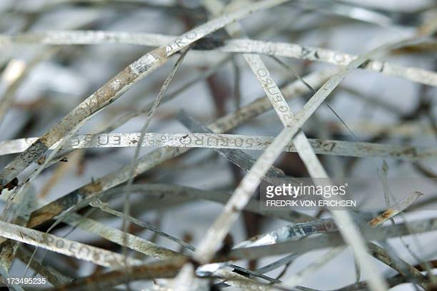 Security threads of flooddamaged fifty euro banknotes are pictured at the counterfeit analysis center of the German Federal Bank in Mainz Germany on...