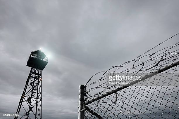 Security tower and razor wire-topped  fence