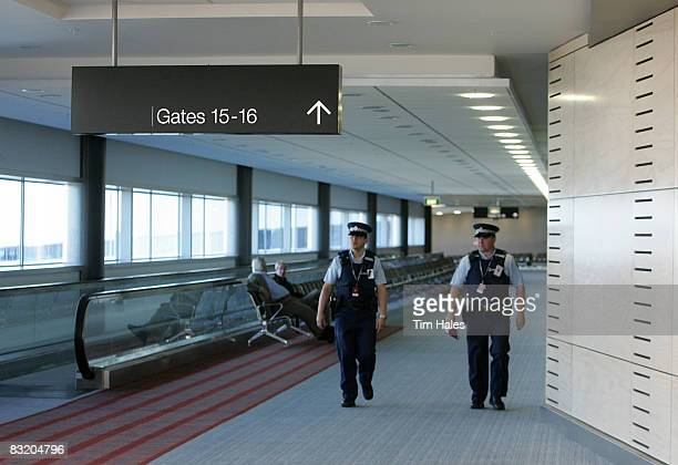 Security walks by a sign that points to Gates 1516 inside of the new pier at Auckland International Airport October 10 2008 in Auckland New Zealand...