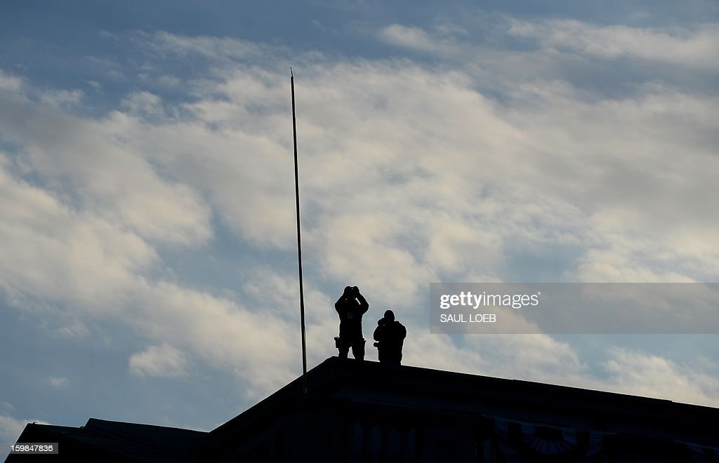 Security watch from the roof of the Treasury Department as US President Barack Obama and First Lady Michelle Obama's motorcade travels along Pennsylvania Avenue during the parade following Obama's second inauguration as the 44th US president on January 21, 2013 in Washington, DC. AFP PHOTO / Saul LOEB