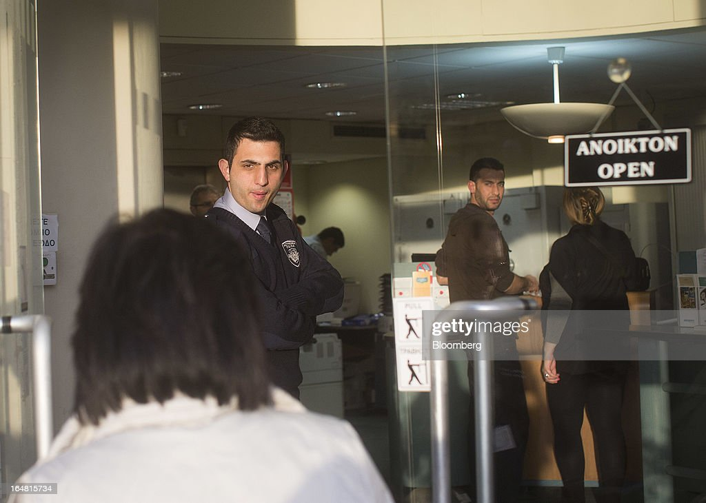 A G4S security watches as a customer enters a Bank of Cyprus Plc branch. as banks open for the first time in two weeks in Nicosia, Cyprus, on Thursday, March 28, 2013. The Central Bank of Cyprus's capital controls will include a 300-euro ($383) daily limit on withdrawals and restrictions on transfers to accounts outside the country. Photographer: Simon Dawson/Bloomberg via Getty Images