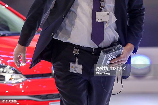 A security worker removes a prop marked 'cheat' left by comedian Simon Brodkin during a protest at a news conference on the Volkswagen AG stand on...