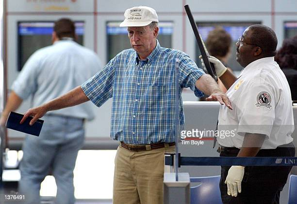A security worker with the Transportation Security Administration screens a traveler September 10 2002 in Terminal 1 at O'Hare International Airport...