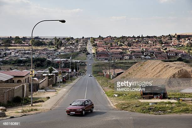 A sedan car approaches an intersection in Soweto on April 15 2014 where in the background visible a recently build urban development With narrow...