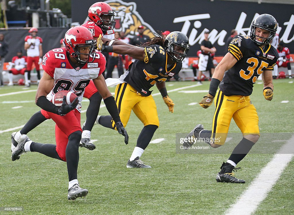 Sederrik Cunningham of the Calgary Stampeders runs with the ball against the Hamilton TigerCats in a CFL game at Ron Joyce Stadium on August 16 2014...