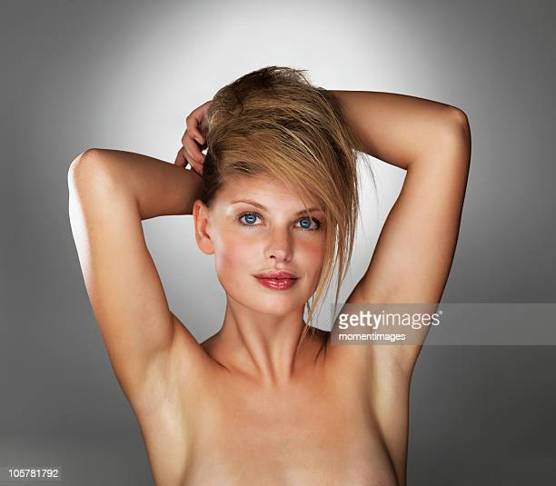 Seductive blond woman with her hands behind her head