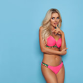 Sexy and beautiful blond woman in pink bikini is holding finger on lips and looking away. Three quarter length studio shot on turquoise background