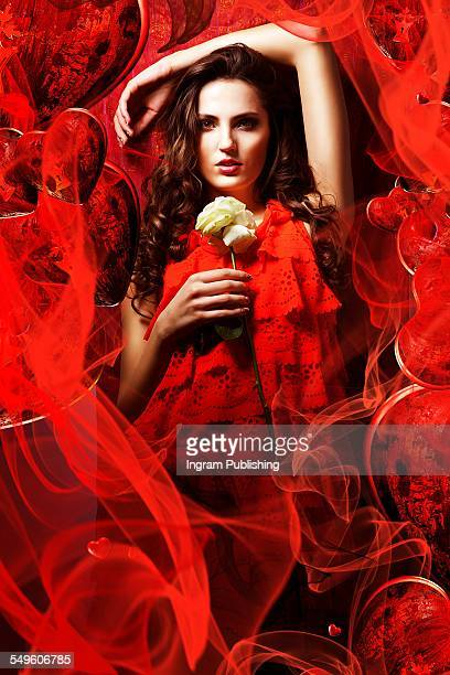 Seductive woman in red dress holding rose