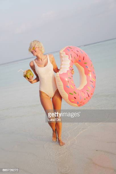 Seductive woman in white swimsuit enjoying in coconut water on Maldives