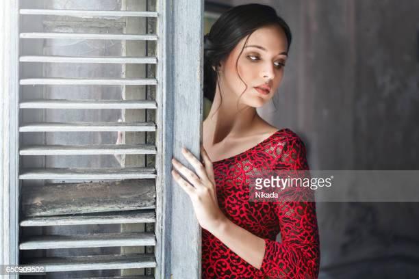 Verleidelijke jonge vrouw leunend op de deur thuis