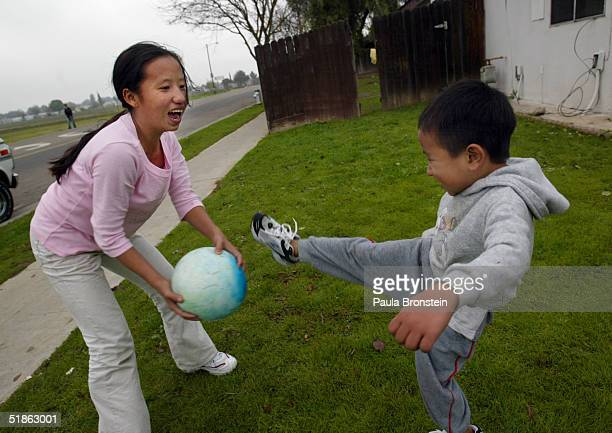 See Vang age13 plays ball with her brother Pa Choua age 7 in front of their home December 12 2004 in Fresno California The Vang family is getting...