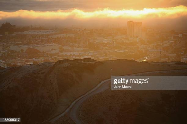 Seen at sunset the USMexico border fence separates Tijuana Mexico from San Diego as a bank of fog rolls in from the Pacific Ocean on November 14 2013...