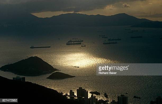 Seen from a hilltop an aerial landscape of Lantau Island and cargo shipping at anchor in West Lamma Channel in the Hong Kong Territories With a pool...