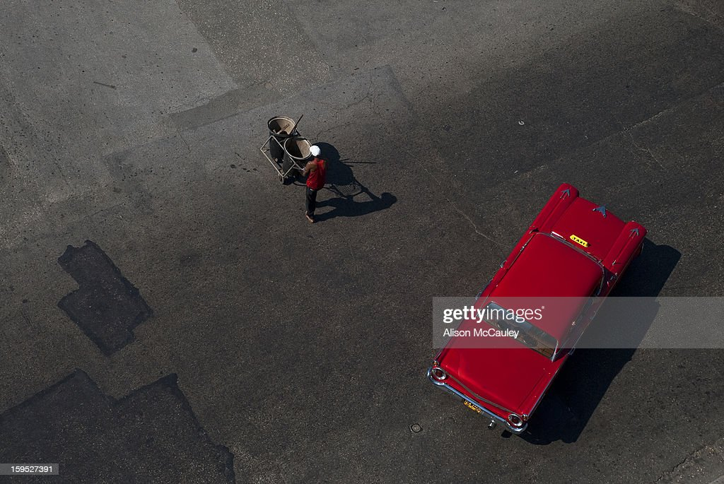 CONTENT] Seen from above, a road sweeper in a red top walks past a red, classic old American car in Havana. The surface of the road is an interesting patchwork of repair works.