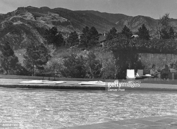 Seen from across the pool of the luxurious Garden of the Gods Club at Colorado Springs is the marred mountainside where the Castle Concrete Co is...