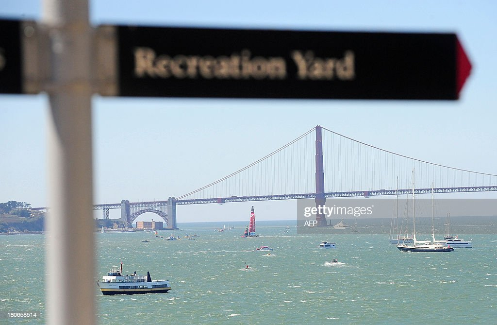 Seen from Alcatraz Island, Emirates Team New Zealand sails near the Golden Gate Bridge before the start of the ninth race of the 34th America's Cup on September 15, 2013 in San Francisco. AFP PHOTO/Josh Edelson