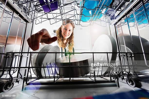 Visto dall'interno lavastoviglie, graziosa Ragazza sorridente di carico o scarico