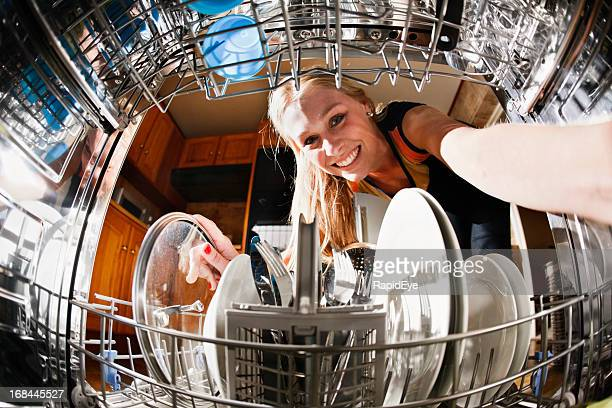 Seen from inside drum, pretty blonde loads the dishwasher