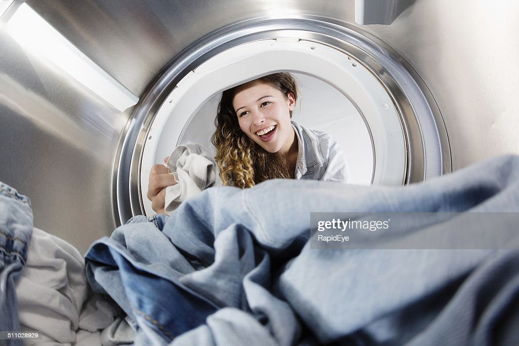 Seen from inside drum, pretty woman loading washing machine