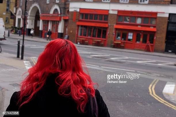 Seen from the rear an anonymous redhaired woman walks towards a business using red as its theme of frontage in north London Dyed as bright as a prime...