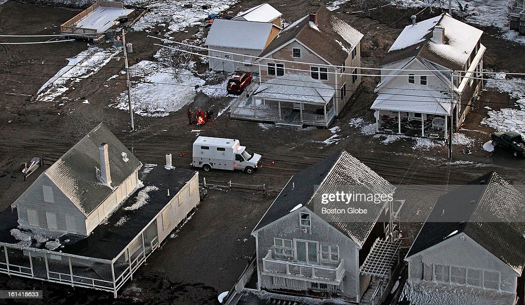 Seen in an aerial view, people keep warm around a fire in a barrel in Scituate, where there is no power, as night sets in on Sunday, Feb. 10, 2013, after a blizzard hit New England.
