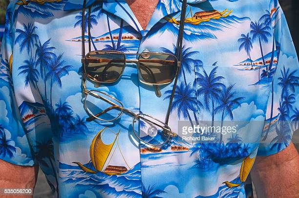 Seen in closeup detail a holidaymaker's shirt is displayed in Magaluf He has two pairs of spectacles hanging around his sunburned neck and a printed...