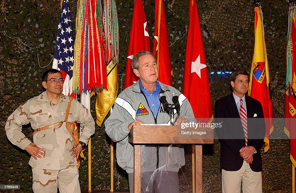 Seen in this handout photo provided by the U.S. Army, President George W. Bush (C) speaks to the troops as Lt. Gen. Ricardo S. Sanchez (L) and Paul Bremer listen, during a surprise visit on Thanksgiving Day, November 27, 2003 in Baghdad, Iraq.