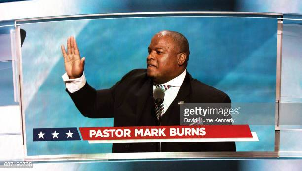 Seen on a large screen above the stage American televangelist Pastor Mark Burns speaks during the Republican National Convention at Quicken Loans...