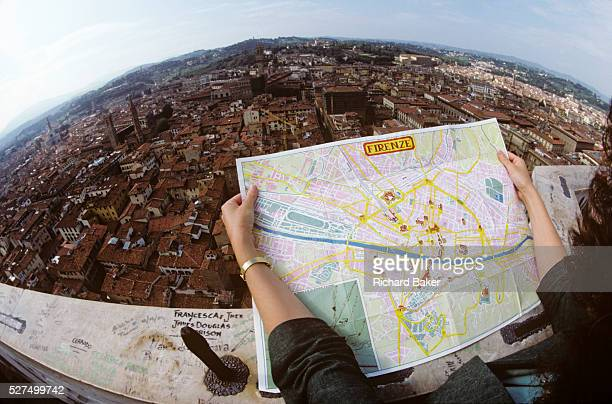 Seen through a fisheye lens we see an aerial view of the city of Florence as a lady tourist surveys the urban landscape using a tourist map She has...