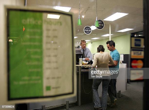 Seen through a window and visible between posted office hours and accepted credit cards an HR Block tax preparer takes payment for income tax...