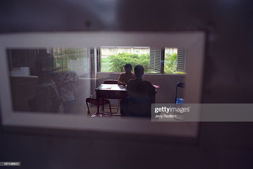 Seen through an examination room window, psychiatrist Ang Sody talks with a patient in a new examination room at the Preah Norodom Sihanouk Hospital in Phnom Penh. The Psychiatric Outpatient Department at the hospital draws several hundred patients a day from Phnom Penh and the surrounding provinces..