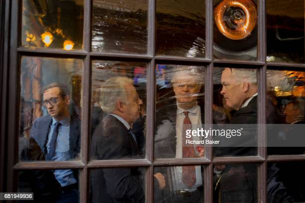 Seen through the distorting glass of a City pub on Lime Street male businessman enjoy afterwork drinks on 10th May 2017 in the City of London England