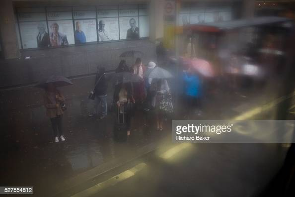 Seen through upperdeck window condensation a crowd of waiting passengers use umbrellas at a bus stop during damp gloomy weather in central London Low...