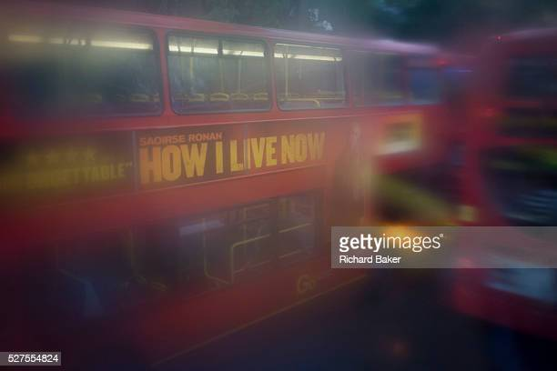 Seen through upperdeck window condensation buses and traffic during damp gloomy weather in central London Low visibility and rain streaks obscures a...
