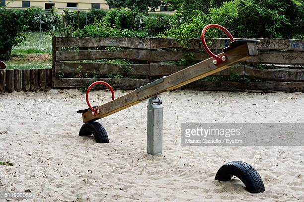 Seesaw in an empty playground with old fence in the background