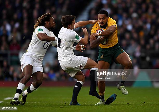 Sefanaia Naivalu of Australia is tackled by Marland Yarde of England and George Ford of England during the Old Mutual Wealth Series match between...