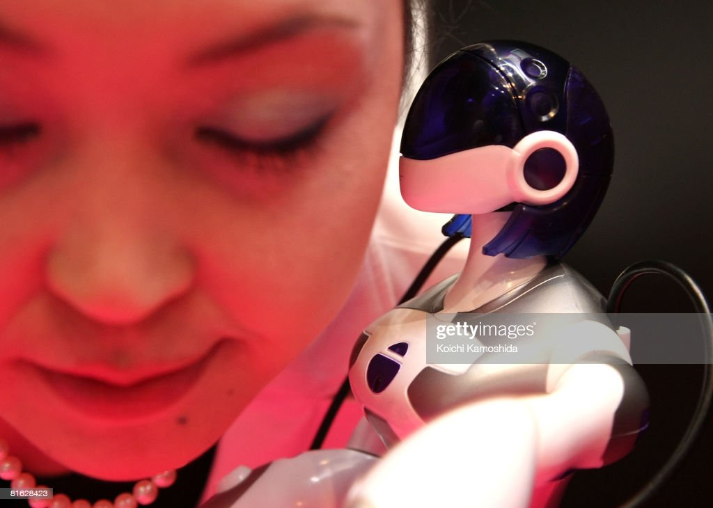 A Sega Toys new female shaped humanoid robot called the 'E.M.A.' (Eternal maiden Actualization) kisses to the model during the International Tokyo Toy Show 2008 at Tokyo Big Sight on June 19, 2008 in Tokyo, Japan. The show will be held unitl June 22. 120,000 people are expected to visit the show over the 4 days which has 134 toy manufacturers from both Japan and abroad showing 36,000 products.