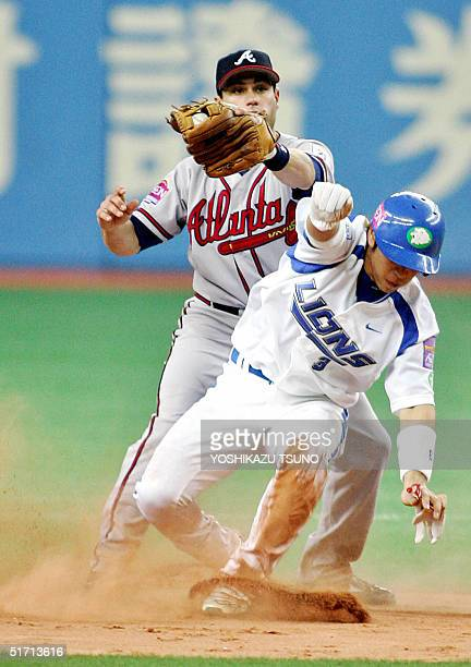 Seibu Lions' Hiroyuki Nakajima steels second base while Atlanta Braves' second base man Marcus Giles grabs the ball during the friendly match between...