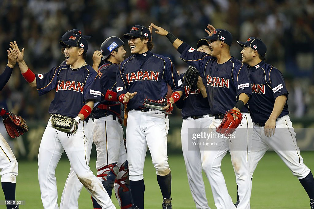 Seiichi Uchikawa and Yoshio Itoi of Team Japan celebrate with teammates defeating Team Chinese Taipei in extra innings in Pool 1 Game 2 in the second...