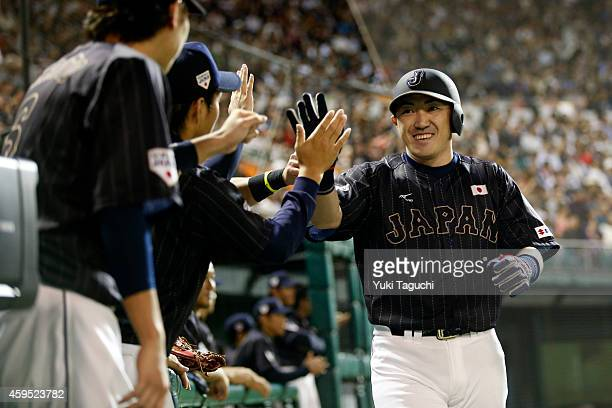 Seiichi Uchikawa of Samurai Japan is greeted in the dugout after scoring a run in the second inning against the MLB AllStars during the game at...