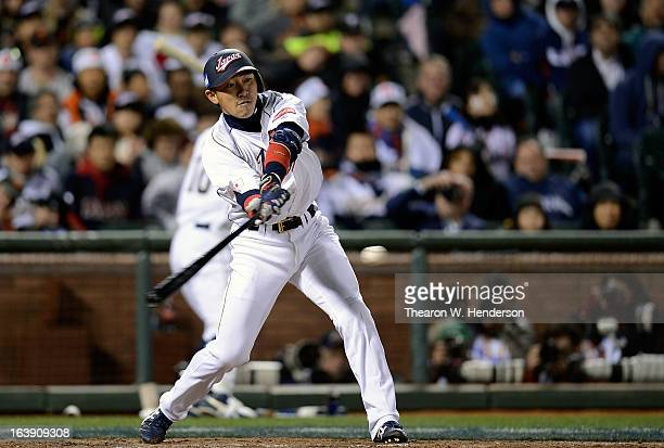 Seiichi Uchikawa of Team Japan hits a triple that just gets by the sliding Angel Pagan of Team Puerto Rico in the six inning during the World...