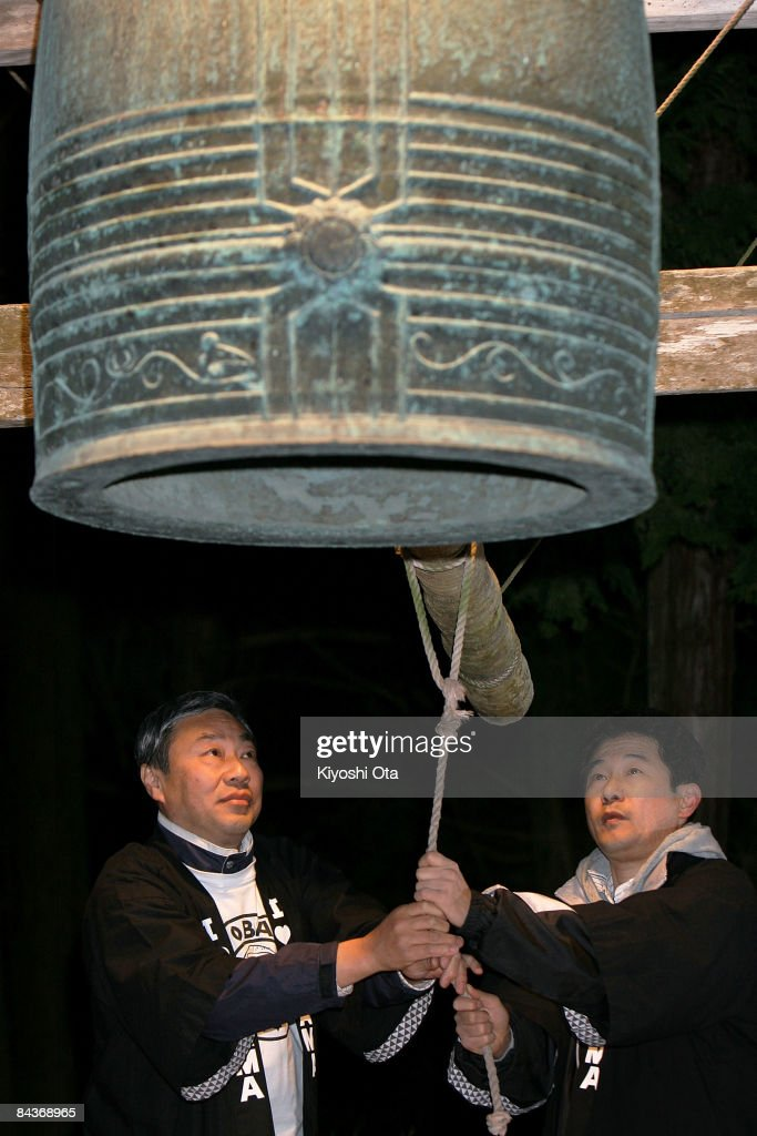Seiji Fujihara secretary general of the local support group 'Obama for Obama' and its group member Yasunori Maeno strike a bell to celebrate the...