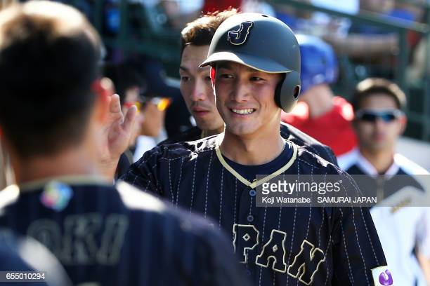 Seiji Kobayashi of Japan hits a single celerates after scoring in the top half of the eigth inning during the exhibition game between Japan and...