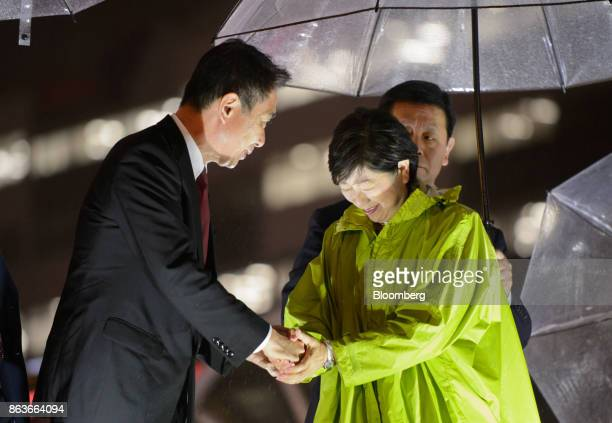 Seiji Maehara leader of the Democratic Party left shakes hands with Yuriko Koike governor of Tokyo and leader of the Party of Hope during an election...