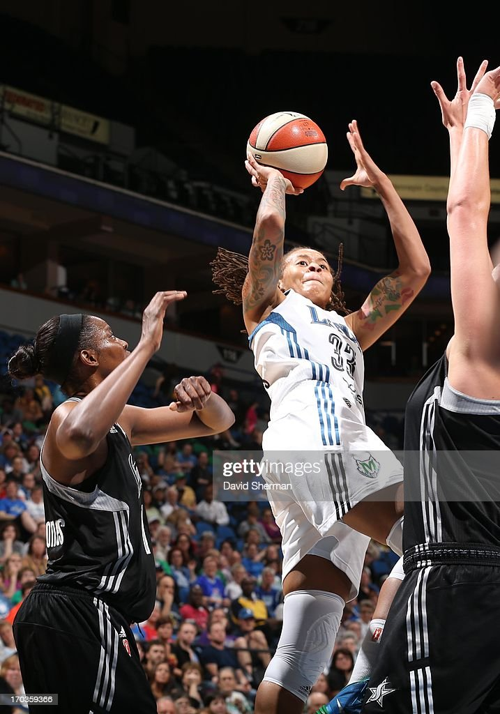 Seimone Augustus #33 of the Minnesota Lynx attempts to shoot over Jia Perkins #7 and Jayne Appel #32 of the San Antonio Silver Stars during the WNBA game on June 11, 2013 at Target Center in Minneapolis, Minnesota.