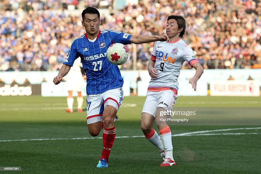Seitaro Tomisawa (L) of Yokohama F.Marinos and Naoki Ishihara of Sanfrecce Hiroshima compete for the ball during the 93rd Emperor's Cup final between Yokohama F.Marinos and Sanfrecce Hiroshima at the National Stadium on January 1, 2014 in Tokyo, Japan.