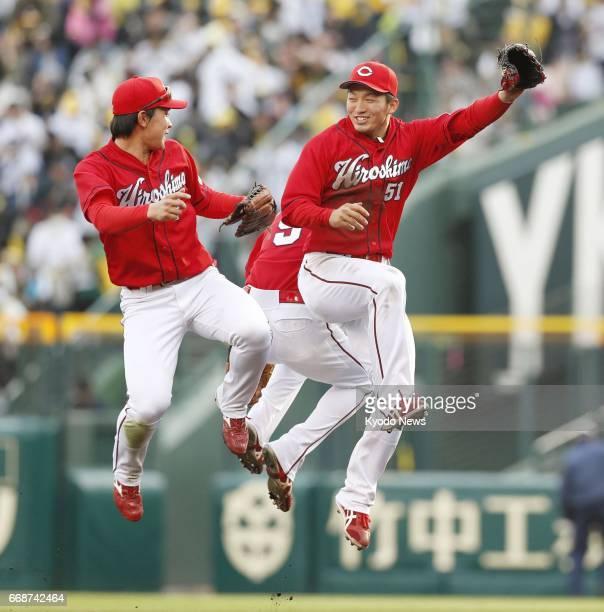 Seiya Suzuki celebrates with fellow Hiroshima Carp outfielders after a 71 win over the Hanshin Tigers at Koshien Stadium in Nishinomiya Japan on...