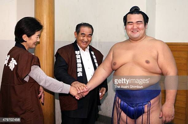 Sekiwake Kotoshogiku shakes hands with his parents as he secures the promotion to Ozeki second highest rank in sumo during the day fifteen of the...
